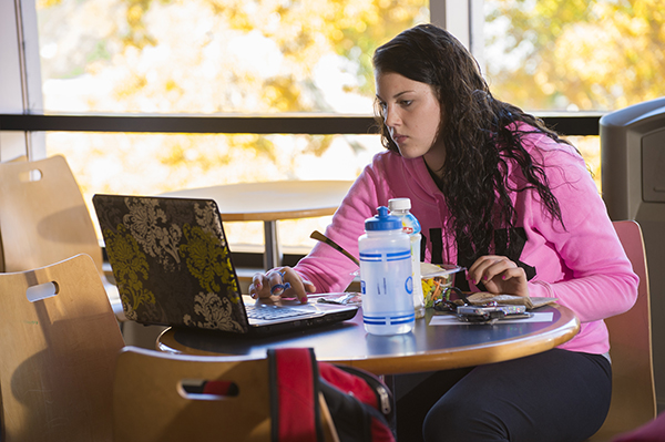 Student working at a laptop while eating