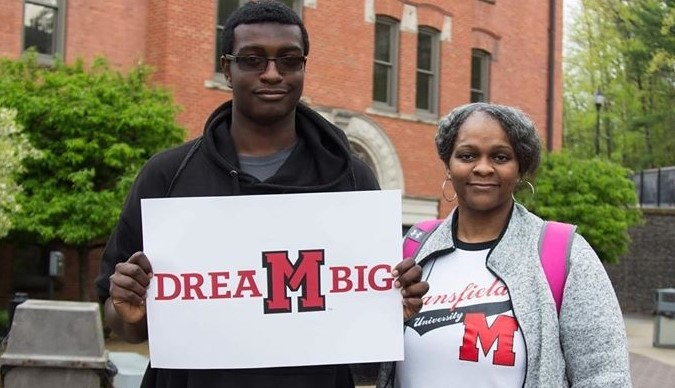 An MU student standing next to his friend and holding a sign reading Dream Big